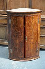 An unusual late 18th Century pollard oak bowfront hanging corner cupboard,