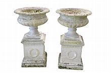 A pair of reconstituted stone garden urns on plinths Each of square section