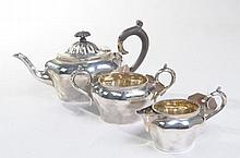 A Edward VII silver three piece tea service Comprising teapot with ebonised loop handle and finial, together with a milk jug and sucrier, each with scrolling loop handles, A & J Zimmerman Ltd, Birmingham, 1903, 17.3oz, teapot 12cm high (3).