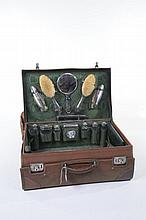 A vintage leather travelling vanity case The hinged cover initialled LMB with a green sateen lined interior and fitted with a silver mounted time piece with a 5.5cm white dial with subsidiary seconds hallmark London 1913, a pair of oval clothes