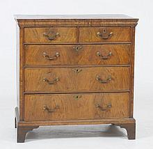 A George II walnut and pine chest of drawers. With a moulded cornice above two short and three long graduated drawers, each with herringbone borders, gilt metal handles, raised upon a shaped plinth and bracket feet with alterations.  103x101x56cm