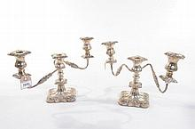 A pair of Elizabeth ll hallmarked silver two branch candelabra With curvilinear bases stamped with blooms and leaves rising to vase shape candle holders, each branch decorated with leaves detachable sconces, made by Viner's Limited, Sheffield 1957,