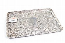 An Edward VII embossed silver tray Of rectangular form with upright fluted gallery edge, the central vacant cartouche amidst rocaille, floral and putti mask designs, William Comyns & Sons, London, 1903, 9.2oz, 26x18cm.