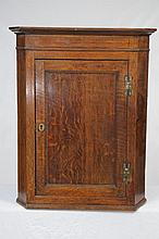 An early 19th Century oak hanging corner wall cupboard With a cavetto cornice above a panelled cupboard door with ''H'' brass hinges enclosing two shelves,91x45cms.