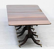 A George III style mahogany four pillar extending dining table The rectangular reeded top with rounded corners enclosing five leaves raised upon four turned barrel shaped shafts, fluted quadruple down swept legs brass shoes and castors 71cm high x