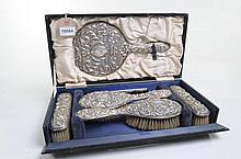 A George V six piece silver backed brush set Comprising two long handled brushes, two further brushes, a comb and a hand mirror all with embossed foliate designs each with vacant cartouche set within original fitted box, W.I. Broadway & Co,