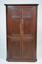A 19th Century oak free standing corner wall cupboard With a shaped over hanging pediment above a plain frieze and a pair of panelled cupboard doors enclosing shelves, the lower part with two panel cupboard doors raised upon a shaped moulded plinth,
