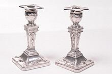 A pair of Edward VII dwarf table candlesticks Each in the Adam style with square canted beaded bases stamped with classical urns rising the vase shaped columns decorated with rams masks and ribbon tied harebells and leaf decorated candle holders with