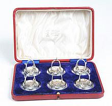 A collection of six Edward VII menu holders Each with circular swept base engraved with a stag monogram raising to a stirrup form card holder, Levi & Salaman, Birmingham, 1907, total weight 2.9oz, in original leather clad box tooled with the initials