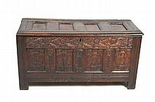 A 17th Century oak four panel blanket chest The rectangular hinged four panel lid with a moulded border above a strapwrork frieze of scrolling leaves, each panel centred with a flowerhead, leafy angles raised upon channelled stile feet, carved sides