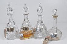 A pair of vase shaped decanters and stoppers Each with pineapple shaped finials overall cut with facets, a similar decanter approximately 32cm, a clear glass mallet shaped decanter engraved with fern leaves each with hall mark silver labels brandy,