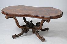 A fine and rare burr walnut centre table The curvilinear well figured quarter veneered top with a leaf carved border against a pounced ground plain frieze with an out swept egg and tongue border raised upon quadruple scrolling leaf carved supports