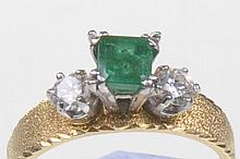 An emerald and diamond set dress ring, 1960's The central square step cut emerald of approx 4.5x4.55mm, four claw set to a round brilliant cut diamond to either side, the stones raised above the satin finish 18ct gold tapering band, estimated total