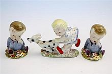 Two Wade 'Wynken Blynken' figurines seated on a floral decorated circular base, one with gold stamp, the other with green stamp,