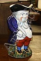 A large Staffordshire Toby Jug late 19th century, with rosy cheeks wearing a blue jacket and red trousers, with a green sponged base,