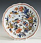 A Rouenware polychrome faience plate 18th century, blue tinted glaze, shaped rim decorated with iron red overlapping hooped border,