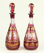 A pair of Bohemian gilt and ruby flashed glass decanters late 19th century, with panel, printie and prism cut decoration,
