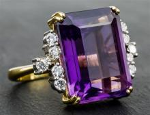 A yellow gold, amethyst and diamond ring the large emerald cut amethyst set with five brilliant cut diamonds to each shoulder,