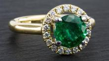 An 18ct yellow gold,, emerald and diamond halo cluster ring