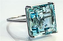 An 18ct white gold and aquamarine ring the 19.63 carat emerald cut aquamarine in an open basket setting, ring size M½.