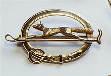 A 15ct yellow gold fox hunting brooch designed as an oval collar crossed by a riding crop and running fox, 3.5cm. across.
