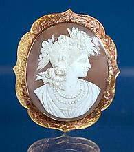 A late Victorian or Edwardian 15ct gold shell cameo brooch the oval cameo carved in high relief with the profile of a classical maid...