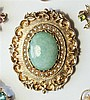 A 9ct gold, seed pearl and green hardstone brooch Victorian style, the oval brooch with foliate scroll border and mated ground,