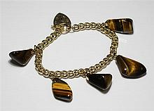 A 9ct gold curb link charm bracelet with padlock clasp and five polished tiger's eye fobs on rolled gold mounts.