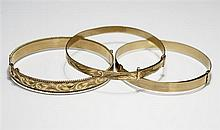 Three 9ct gold bangles two of expanding design, on plain and one foliate engraved, the other hinged with clasp. (3)
