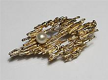 A 9ct gold and pearl bark effect brooch 1970s, the open bark effect brooch set with a single 5.2mm. cultured pearl,