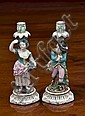A pair of Derby style porcelain candlesticks early 19th century, emblematic of the seasons, one with a boy, arms folded,