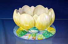 A Clarice Cliff centre piece modelled as a water lily, pattern number 973, stands on oval blue wash and foliate base,