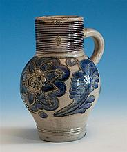 An 18th century stoneware Westerwald ale jug drum form upper section with horizontal combed decoration with manganese glaze above a...
