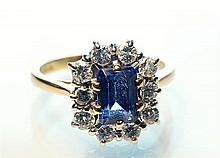 An 18ct gold, tanzanite and diamond cluster ring the central emerald cut tanzanite, approx. 1.25 carats,