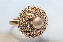 An 18ct yellow gold, diamond and pearl cluster ring the domed floral style ring centred by a single 7mm. pearl,