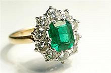An 18ct yellow and white gold, emerald and diamond cluster ring the central emerald of good colour, approx. 3 carats,