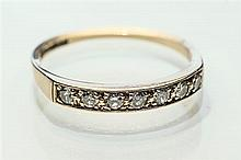 A 9ct yellow gold and diamond ring set with seven small round brilliant cut diamonds, totalling approx. 0.2 carats, ring size N.