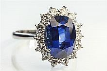 An 18ct white gold, sapphire and diamond cluster ring