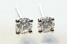 A pair of 18ct white gold and diamond stud earrings the four claw set round brilliant cut diamonds totalling 0.82 carats.