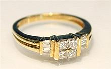 A 9ct yellow gold and diamond ring set with four central princess cut diamonds and three baguette cut diamonds channel set to either...