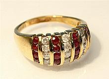 A 9ct gold, ruby and diamond ring set with alternate rows of round cut rubies and round brilliant cut diamonds,