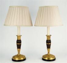 A pair of French patinated bronze and ormolu candlesticks second half of 19th century,