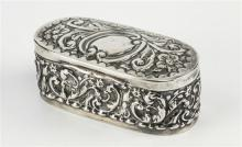 An Edwardian silver pill box William Aitken, Birmingham 1903, rounded rectangular form with repousse scroll work decoration,