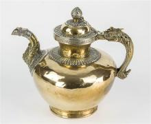 A Tibetan silver and brass teapot 19th century, brass ovoid body on a flared foot, with a makara spout and dragon handle,