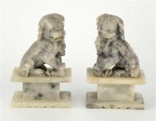A pair of Chinese carved soapstone dogs of fo 20th century, modelled in seated position upon rectangular and block form plinths,