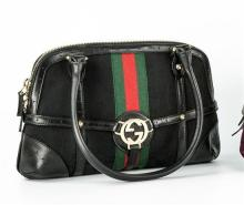 A Gucci handbag black canvas with opposing 'GC' logo, leather straps handles and corners gold metal furniture,