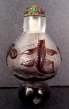A peking glass snuff bottle of carved fish and lotus base