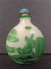 A peking glass snuff bottle carved green figures on white
