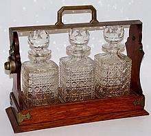 An oak three bottle tantalus with silver plated mo