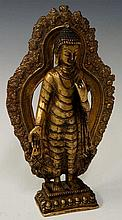 A gilt bronze model of a deity standing before a d
